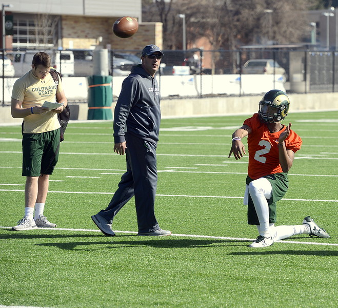 CSU quarterback Justice McCoy throws from his knees in front of quarterbacks coach Ronnie Letson during Wednesday's spring practice. (Mike Brohard/Reporter-Herald)