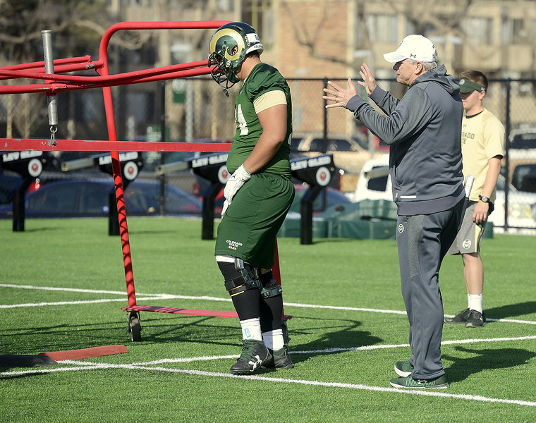 Colorado State offensive line coach Dave Johnson explains a drill as Salofi Gaoa awaits his rep during Wednesday's spring practice. (Mike Brohard/Reporter-Herald)