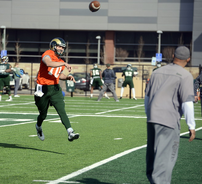 CSU quarterback J.C. Robles gets airborne on his roll-out throw during Wednesday's practice. (Mike Brohard/Reporter-Herald)