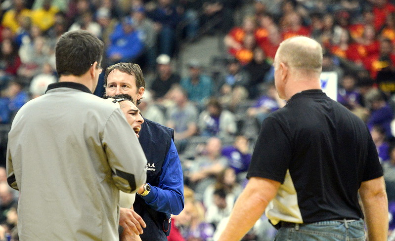 Erik Contreras of Mountain View grimmaces as a trainer looks at his shoulder during Friday's state wrestling semifinals.