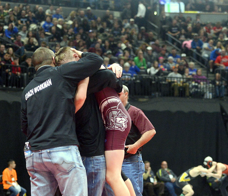 . Berthoud\'s Kolten Strait jumps into the arms of coach Will Carron after winning his 113-pound semifinal Friday night in the 3A state wrestling tournament at the Pepsi Center in Denver.