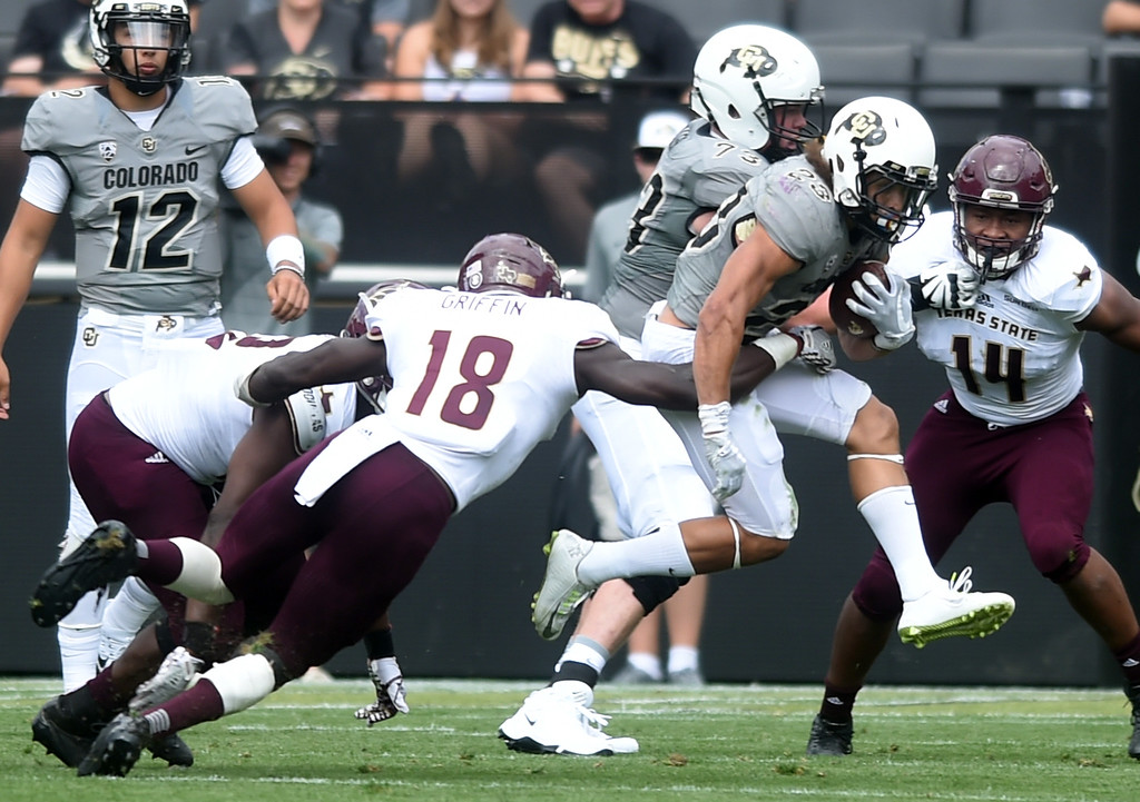 . Phillip Lindsay, of CU, tries to escape Frankie Griffin, of TSU during the game with Texas State on Saturday. For more photos, go to buffzone.com.  Cliff Grassmick / Staff Photographer/ September 9, 2017