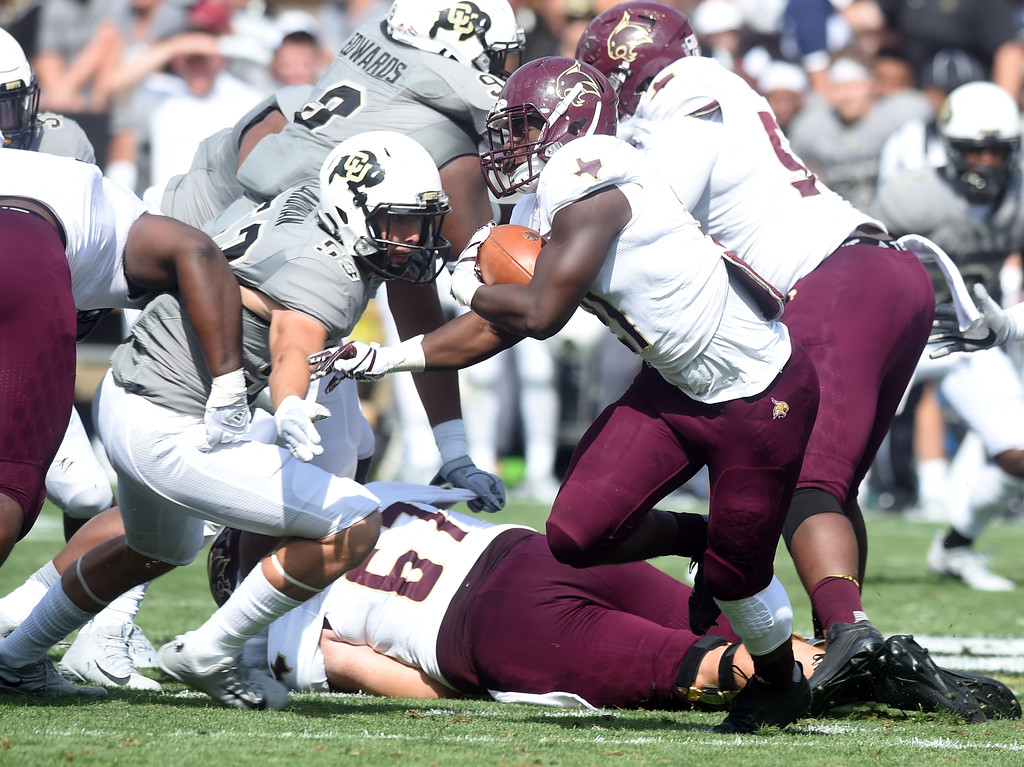 . Anthony Smith, of Texas State, tries to escape the CU defenders during the game with Texas State on Saturday. For more photos, go to buffzone.com.  Cliff Grassmick / Staff Photographer/ September 9, 2017