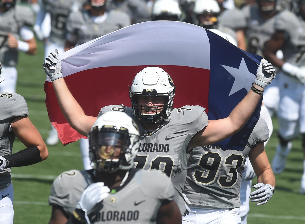 . Jonathan Huckins runs onto the field with a flag before the game with Texas State on Saturday. For more photos, go to buffzone.com.  Cliff Grassmick / Staff Photographer/ September 9, 2017