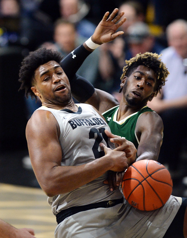 . BOULDER, CO: December 1:  Evan Battey, of CU, and Kris Martin, of CSU, battle under the basket during the Colorado and Colorado State men\'s basketball game. (Photo by Cliff Grassmick/Staff Photographer)