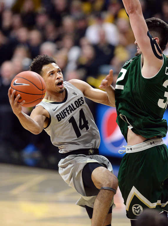 . BOULDER, CO: December 1:  Deleon Brown, of CU, drives on Nico Carvacho, of CSU,  during the Colorado and Colorado State men\'s basketball game. (Photo by Cliff Grassmick/Staff Photographer)