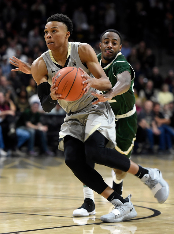 . BOULDER, CO: December 1:  Shane Gatling, of CU, drives past JD Paige, of CSU,  during the Colorado and Colorado State men\'s basketball game. (Photo by Cliff Grassmick/Staff Photographer)