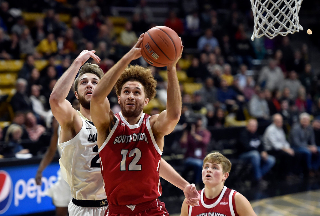 . BOULDER, CO - DECEMBER 4, 2018: University of South Dakota\'s Trey Burch-Manning snags a rebound over Lucas Siewert  during a NCAA game against the University of Colorado on Tuesday at the Coors Event Center on the CU campus in Boulder. More photos: Buffzone.com (Photo by Jeremy Papasso/Staff Photographer)