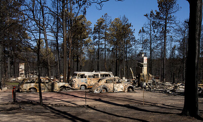 Three autos and the remains of two fireplaces from separate houses.