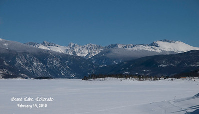Rocky Mountains on the other side of snow and ice covered Grand Lake.