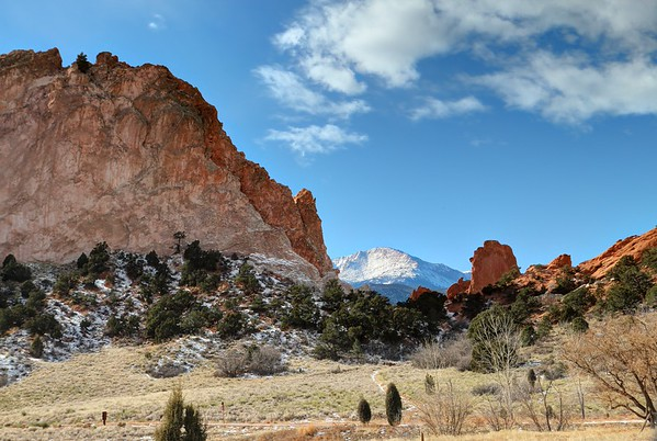Snow covered mountains from the Pikes Peak range fill the background of these massive stone and rock formations in the Garden of the Gods in Colorado.