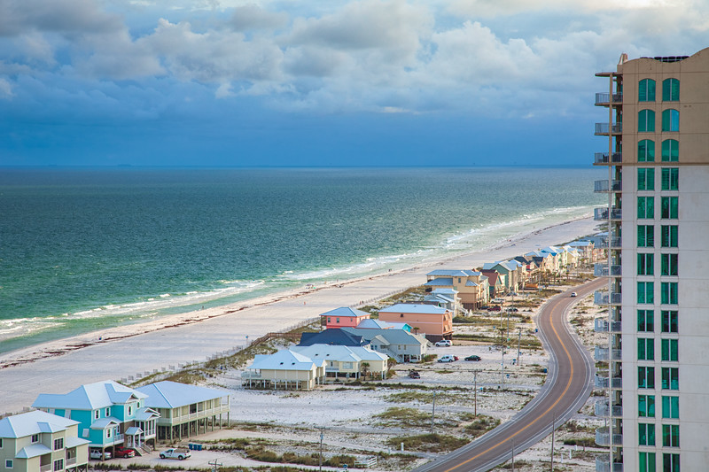 The west side of Gulf Shores, Alabama, looking west along the white sand beach of the Gulf of Mexico.