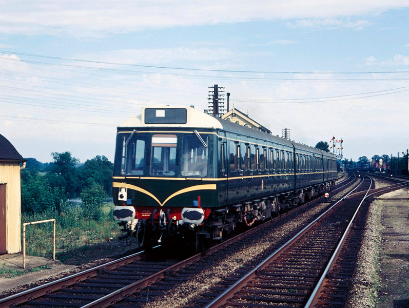 A Western Region DMU photographed passing Tilehurst signal box on the up relief towards Reading:  i.e. the train is moving away from the photographer, which explains the absence of driver!  Beyond this, I am looking for guidance.  Am I correct that this is a Class 117 DMU?  And what about the date?  It is taken on Ferrania colour film which my father didn't use after 1959.  By August 1960 he had moved to Agfa colour film.  It looks to me as though this unit is brand new and, as I understand it, these units were only introduced in 1959?  The only other clue is a second shot probably taken on the same day of a similar unit heading west toward Tilehurst where the destination board seems to read Banbury and the headcode is 2H49.