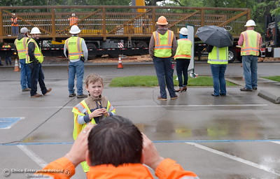 Brendan Ottoboni takes a photo of 4-year-old Domonic Ottoboni while City of Chico construction crews install a footbridge over Comanche Creek Friday May 6, 2016. (Bill Husa -- Enterprise-Record)