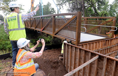 "BCAG employees who work nearby on the Otterson Drive side of the creek take photos as City of Chico construction crews install a footbridge over Comanche Creek Friday May 6, 2016. BCAG Senior Planner Jim Peplow said ""We ride our bikes to work all of the time. This will be a huge savings for us. You don't have to deal with the traffic on Hegan Lane."" (Bill Husa -- Enterprise-Record)"