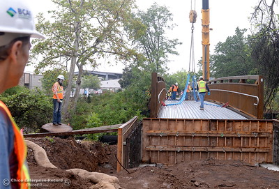 "BCAG employees who work nearby on the Otterson Drive side of the creek watch City of Chico construction crews install a footbridge over Comanche Creek Friday May 6, 2016. BCAG Senior Planner Jim Peplow at left, said ""We ride our bikes to work all of the time. This will be a huge savings for us. You don't have to deal with the traffic on Hegan Lane."" (Bill Husa -- Enterprise-Record)"