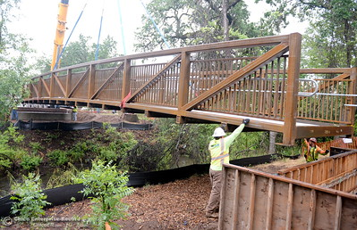City of Chico construction crews line up the bridge as it slides onto bolts during installation of a footbridge over Comanche Creek Friday May 6, 2016. (Bill Husa -- Enterprise-Record)