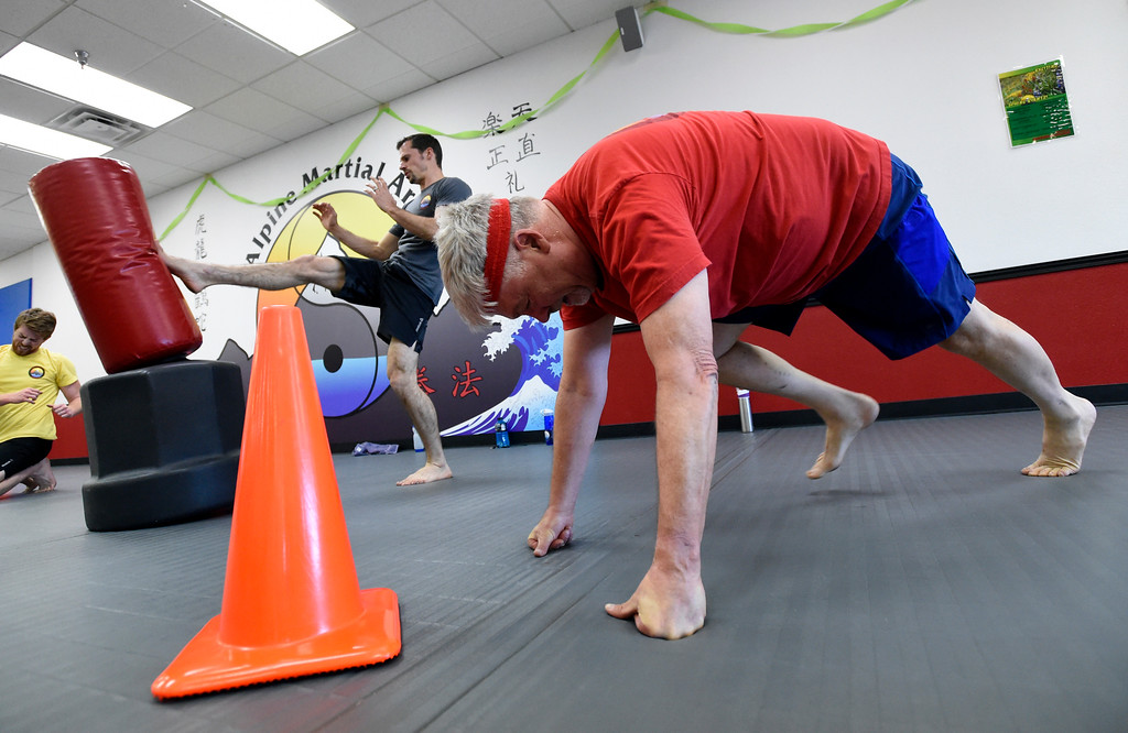 . Owner Brad Randolph, at center, and David James work out during a combat fitness class at Boulder Karate on Wednesday in Boulder. For more photos of the combat fitness class go to www.dailycamera.com Jeremy Papasso/ Staff Photographer/ April 20, 2017