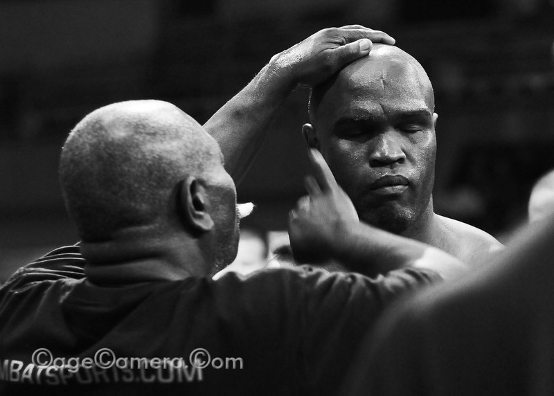 """I always thought the ritual of having petroleum jelly applied to the face right before a fight made for a beautiful moment.    It is the last time a fighter will feel gentle hands on his face and the moment is usually marked with a serene, almost meditiative expression as the invisible warpaint is applied. Here Gary """"Big Daddy"""" Goodridge is anointed with Vaseline before entering the cage to fight Pedro """"The Rock"""" Rizzo."""