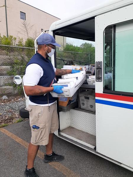Lowell carrier Alex Jorge loads his truck.
