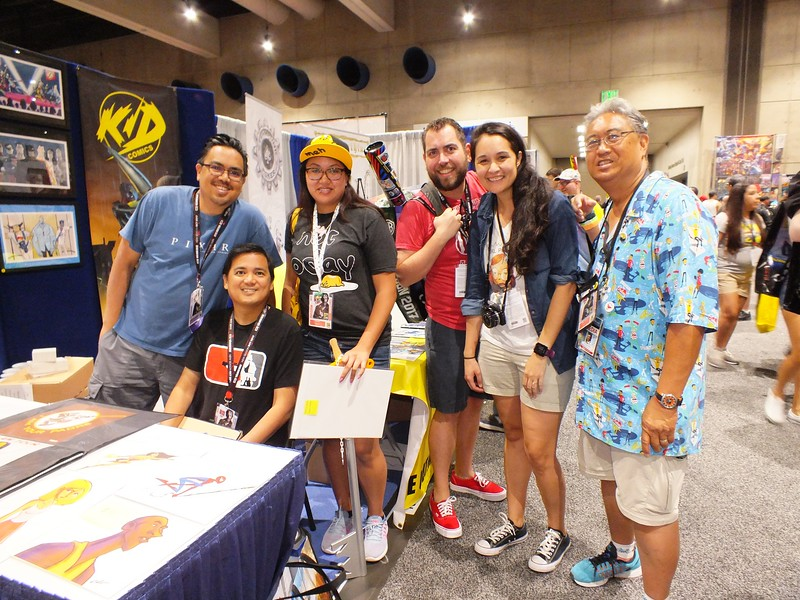 Pixar animator and creator of the popular Alcatraz High comic books, Bobby Rubio (left) is joined by his Warner Bros. Animation Director brother Ronald Rubio (seated) along with fans from the Asian/Pacific American Librarians Association (APALA) at his SDCC booth.
