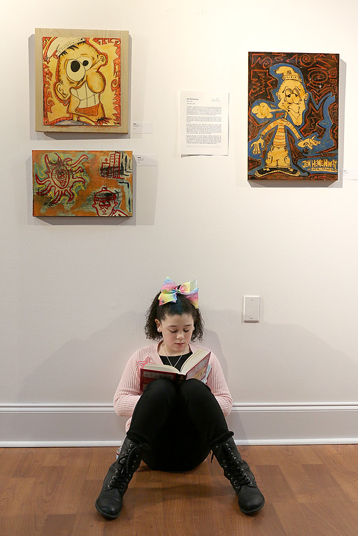 ". Gallery Sitka in Fitchburg held a ""Comics Are Art\"" show on Saturday. Lillianna Secino, 9, of Fitchburg reads her book below some wok in the show by Jen Hemenway. SENTINEL & ENTERPRISE/JOHN LOVE"