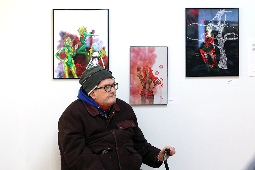 ". Gallery Sitka in Fitchburg held a ""Comics Are Art\"" show on Saturday. Kevin McCarthy sits in front of some art at the show by Adre Mills. SENTINEL & ENTERPRISE/JOHN LOVE"