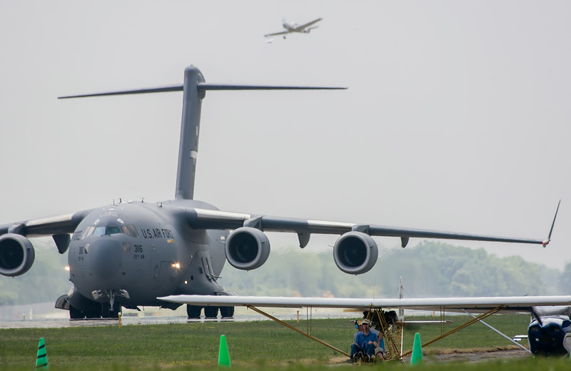 The Large and the Small:  A C-17 rolls out after landing on Runway 36.  Overhead is a sport aircraft; in the foreground a homebuilt and a Cessna.