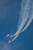 The Thunderbirds dive out of a loop.  Notice the condensation trails the aircraft are generating in the humid Wisconsin air.