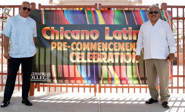 Faculty and Administration members stand along the sides of the sing Chicano Latino Pre-Commencement Celbration sign on the gates of the outdoor theater.