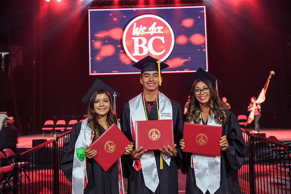 3 graduates in front of We Are BC screen.