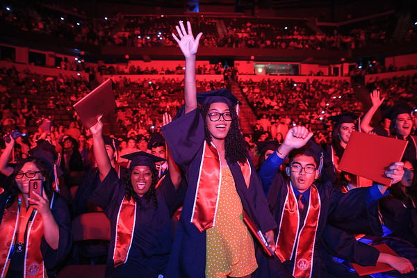 Graduates raising their arms and cheering.
