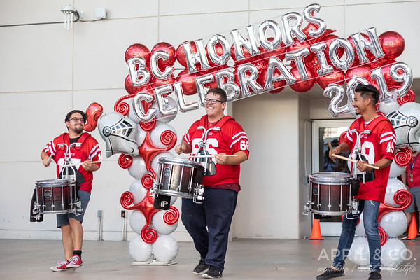 3 drumline drummers smile play in front of the BC Honors Celebration 2019 balloons.