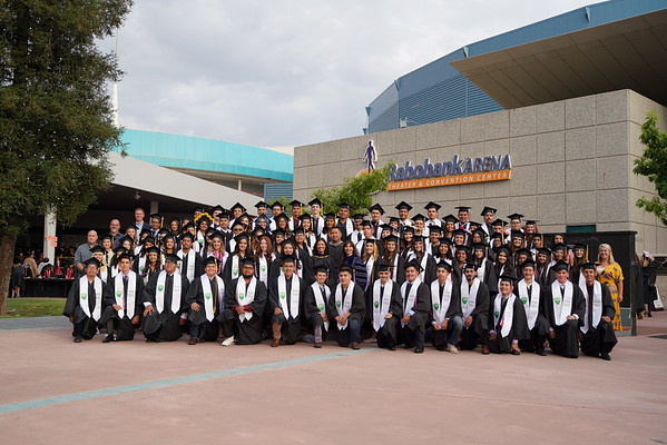 Graduates in full regala in front of the arena.