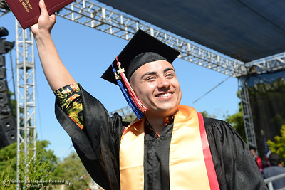 Manuel Ibarra waves his diploma to friends and family in the crowd durign the Chico State commencement ceremony Sunday, May 21, 2017, at University Stadium in Chico, California.  (Dan Reidel -- Enterprise-Record)