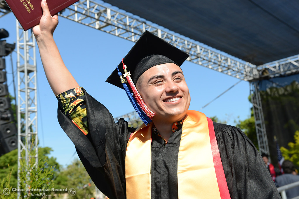 . Manuel Ibarra waves his diploma to friends and family in the crowd durign the Chico State commencement ceremony Sunday, May 21, 2017, at University Stadium in Chico, California.  (Dan Reidel -- Enterprise-Record)