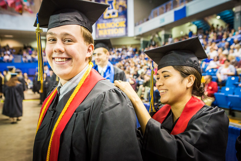 """Shelly DeWilde, right, writes last minute notes on her name card on Luke Dinon during the commencement ceremony at the Carlson Center Sunday, May 8, 2016.  <div class=""""ss-paypal-button"""">Filename: GRA-16-4896-490.jpg</div><div class=""""ss-paypal-button-end""""></div>"""