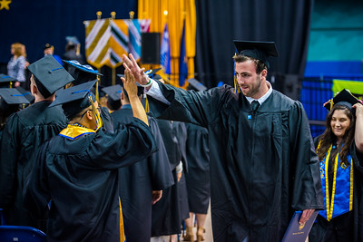 UAF film graduate Mark Stoller high-fives Daniel Nero after both Nero and Stoller received their diplomas at Commencement 2017.