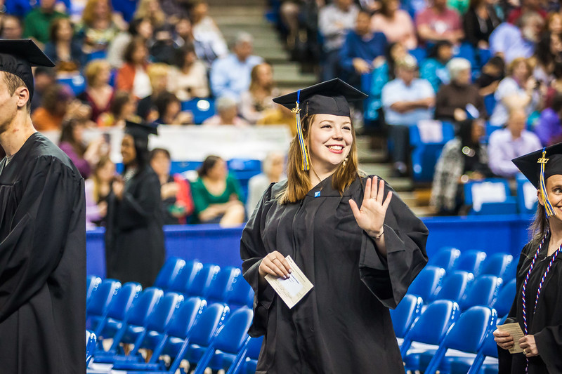 Graduate Anastasia Brease waves to the audience during the 2017 commencement ceremony processional at the Carlson Center Saturday, May 6.