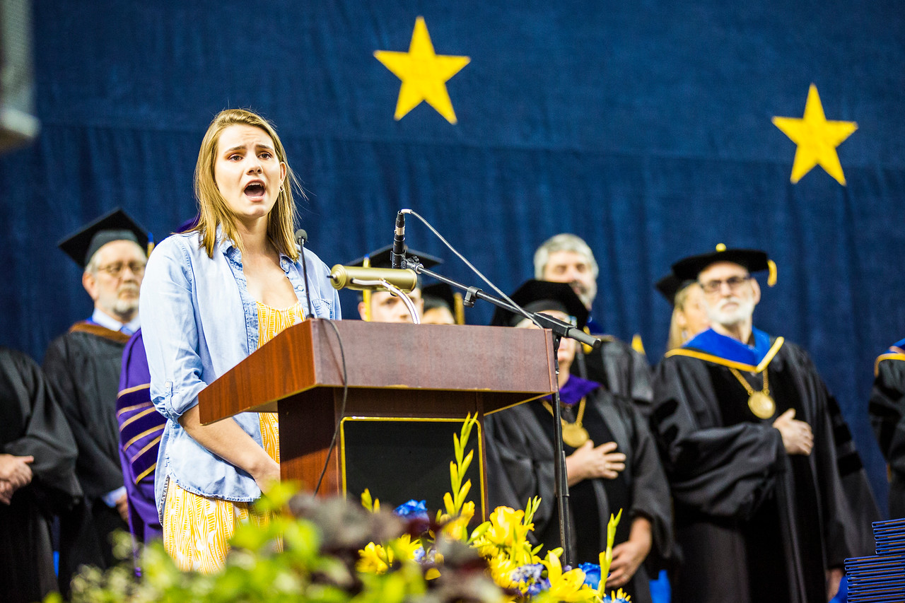 UAF music education major Ariana Horner sings the national anthem during UAF's 2018 commencement ceremony at the Carlson Center on May 5, 2018.