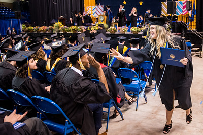Ella Nicole Van Siegman, right, high-fives journalism graduate Terrence Holmes after receiving her bachelor's degree in secondary education at UAF's commencement ceremony at the Carlson Center on May 5, 2018.