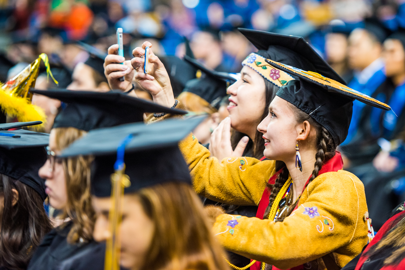 Kk'odohdaatlno Christina Edwin (right), who earned a bachelor's degree in rural development, and Diloola Aanh Erickson (left), who earned bachelor's degrees in both rural development and mechanical engineering, take photos of their classmates during UAF's commencement ceremony at the Carlson Center on May 5, 2018.