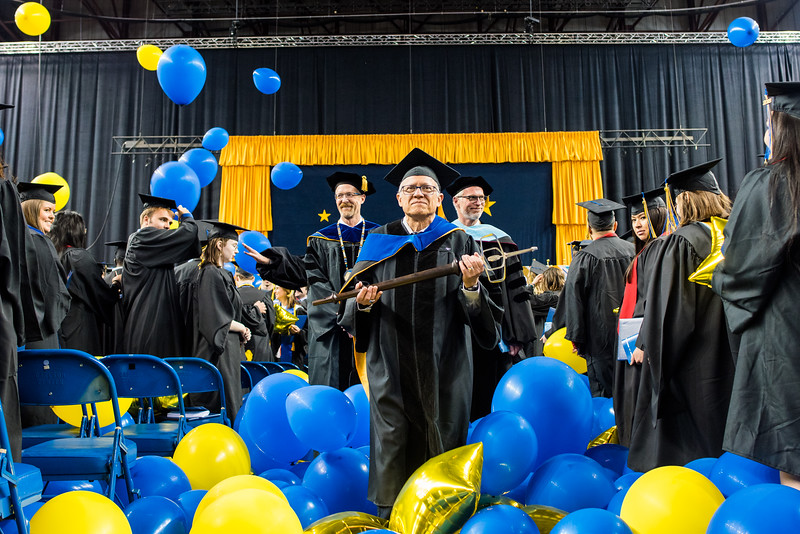 Lawrence Kaplan, professor emeritus of linguistics, bears the university's mace as grand marshal for UAF's commencement ceremony on May 5, 2018, at the Carlson Center.
