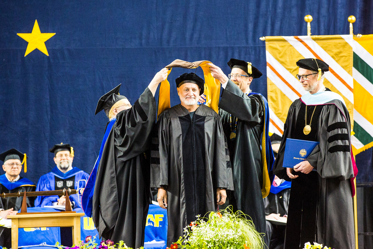 """Musician and songwriter James Milton Varsos, also known as """"Hobo Jim,"""" receives an honorary Doctor of Fine Arts degree during UAF's commencement ceremony at the Carlson Center on May 5, 2018."""