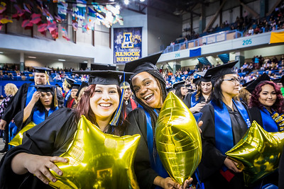 Elizabeth Hinkey, left, and Meisha Hylton, who earned associate degrees from the Community and Technical College, celebrate after UAF's  commencement ceremony in the Carlson Center on May 5, 2018.