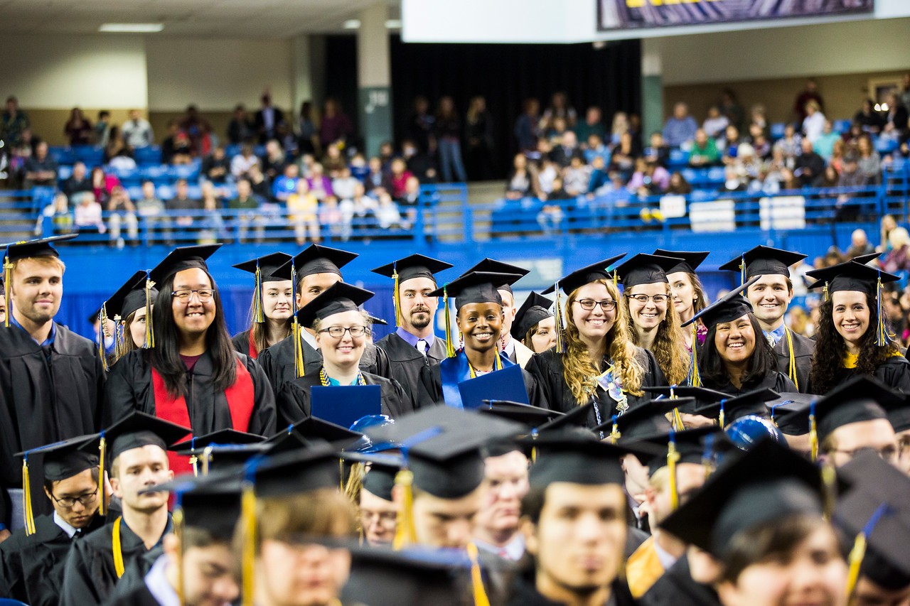 Graduates from the College of Natural Science and Mathematics stand at their seats as their peers walk across the stage during UAF's commencement ceremony at the Carlson Center on May 5, 2018.
