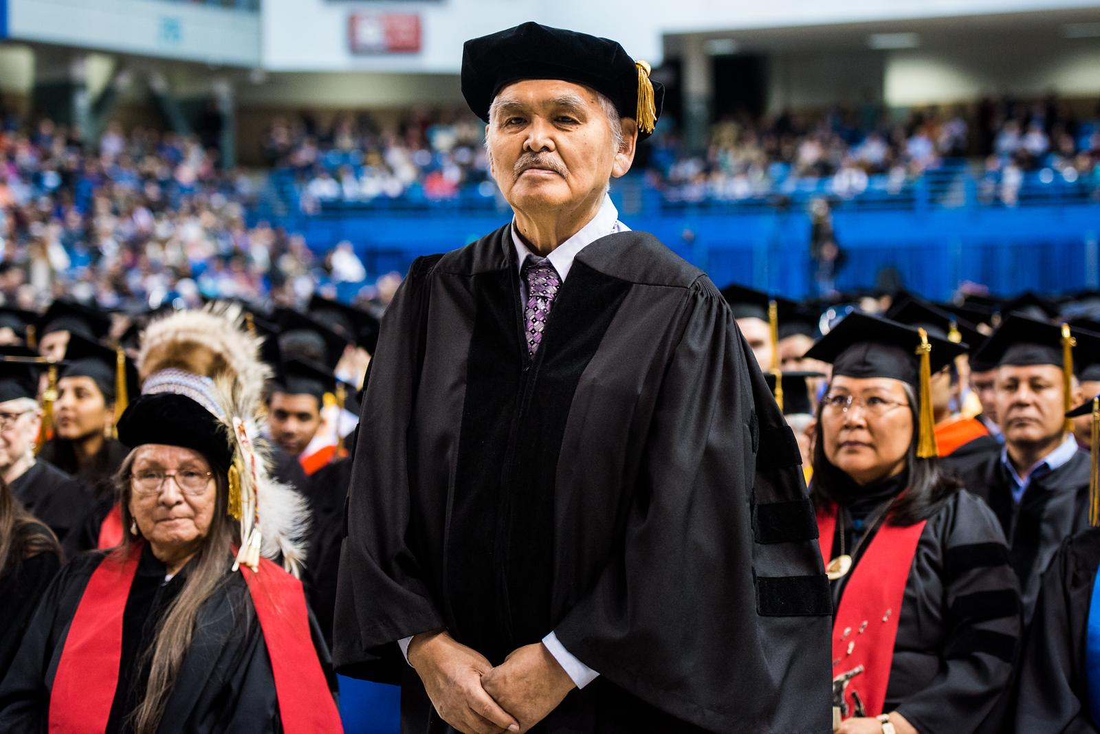 Jacob Anaġi Adams Sr. stands while being recognized for an honorary Doctor of Laws degree during UAF's 2018 commencement ceremony at the Carlson Center on May 5, 2018.