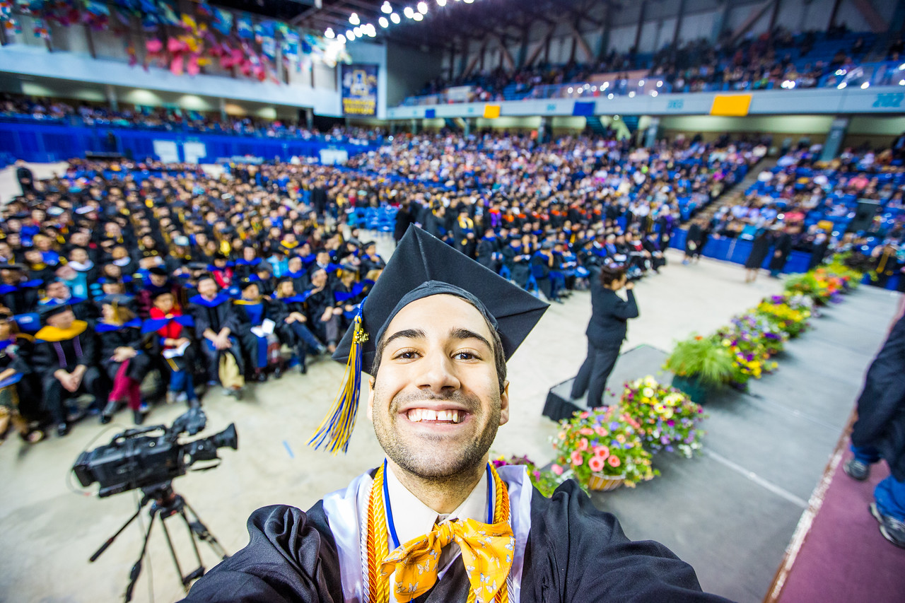 UAF student photographer Zayn Roohi takes a selfie on stage after receiving his bachelor's degree in mechanical engineering at UAF's commencement ceremony in the Carlson Center on May 5, 2018.