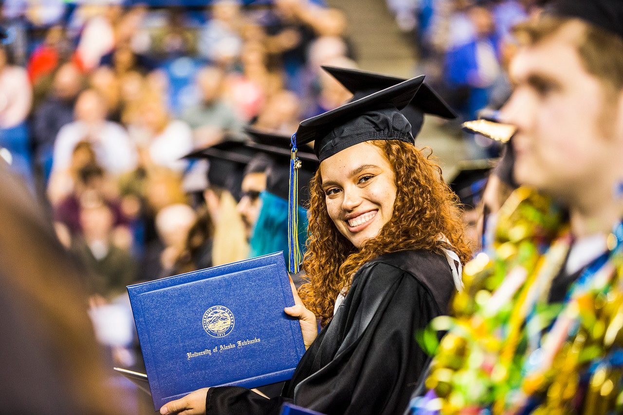Ariana Polanco, who earned a bachelor's degree in theater, displays her diploma book during UAF's commencement ceremony at the Carlson Center on May 5, 2018.