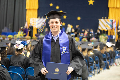 Nathan Taylor, a rifle team member who earned a bachelor's degree in biological sciences, returns to his seat after crossing the stage during the University of Alaska Fairbanks' 97th commencement ceremony on May 4, 2019, in the Carlson Center.